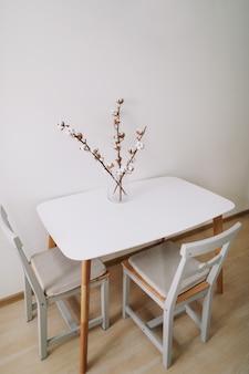 テキストスペースで屋内の白い背景の上の乾燥したふわふわ綿の枝