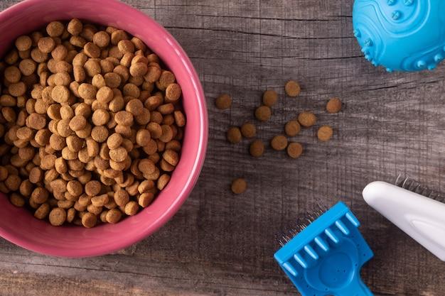 木製の背景に猫の乾燥食品やおもちゃをクローズアップ