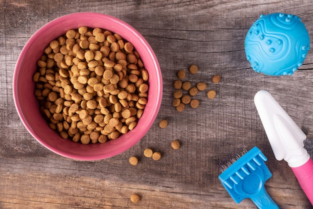 木製の背景に猫のための乾燥食品やおもちゃ