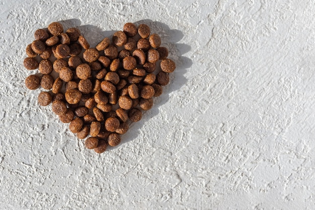 Dry food for dogs and cats in the shape of a heart on a white plaster background, copy space, top view.