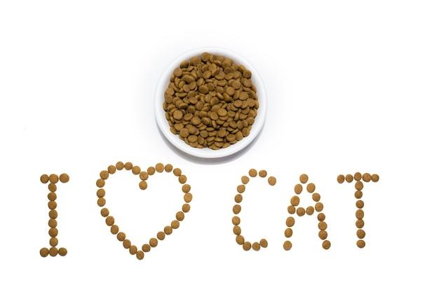 白いボウルに猫と犬のためのドライフード。食べ物からの心。碑文私は猫が大好きです。スタジオの白い背景。高品質の写真