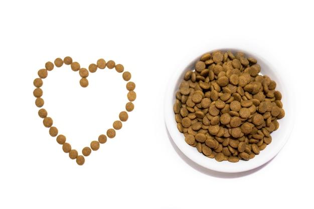 白いボウルに猫と犬のためのドライフード。食べ物からの心。スタジオの白い背景。高品質の写真