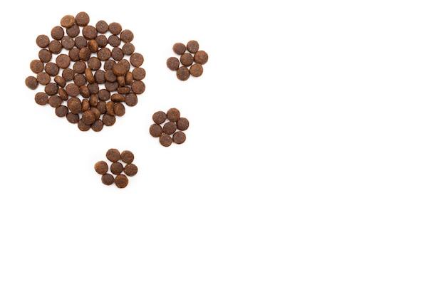 白い背景で隔離の足跡の形で犬や猫のための乾燥食品。猫と犬のための食べ物。健康的なペットフードのコンセプト。