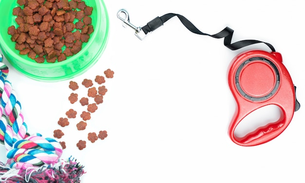 Dry food with pet accessories on white background