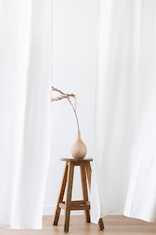 Dry forsythia branch in a wooden vase on a stool by a white curtain