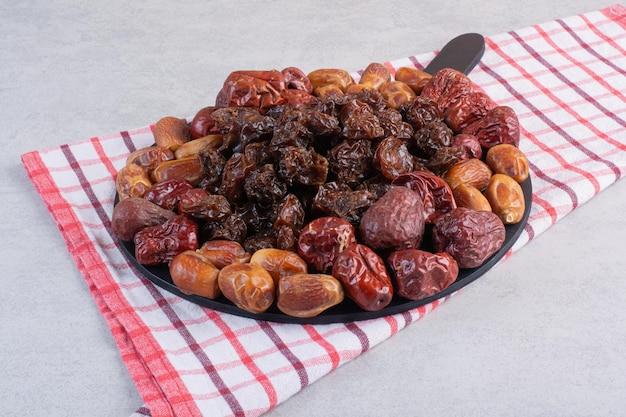 Combinazione di frutta secca su un piatto su una superficie di cemento.