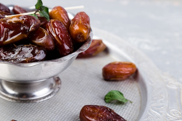 Dry fruit dates on silver tray. copyspace. close up.