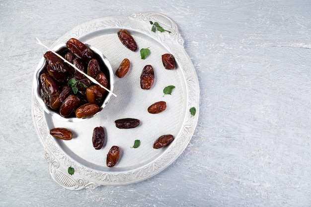 Dry fruit dates on silver tray. copyspace. top view.