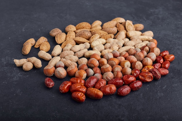 Dry fruits and beans on black surface, angle view.
