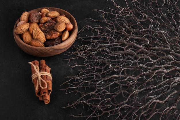 Dry fruits and cinnamons on black background.