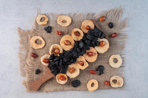 콘크리트 표면에 사과 조각, 검은 술타나, 대추 열매를 포함한 건조 과일.