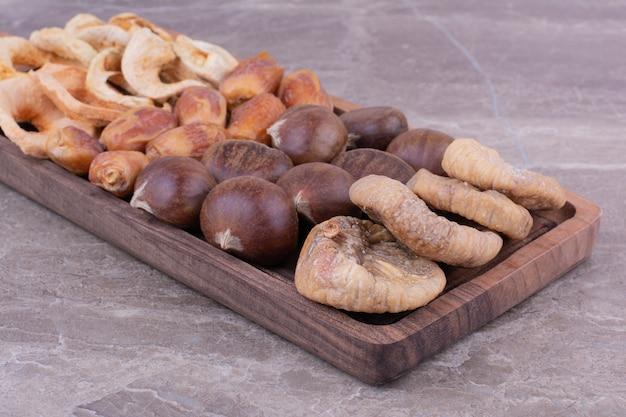 石の上の木製の大皿にドライフルーツ