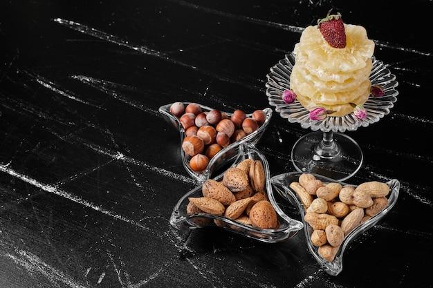 Frutta secca e fette di ananas in piatti di vetro.