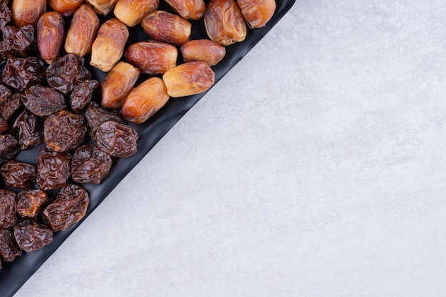 Dry fruits set with dates and cherries on a wooden platter. high quality photo