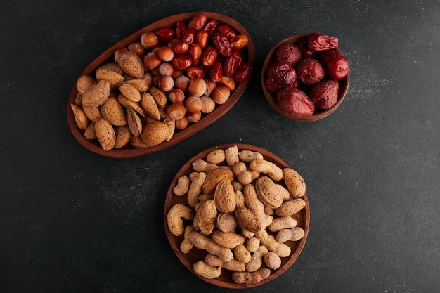 Dry fruits in wooden platters, top view.