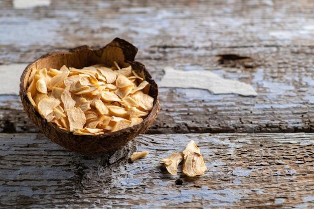 古い木製の背景にココナッツ ボウルにフレークでニンニクを乾燥します。