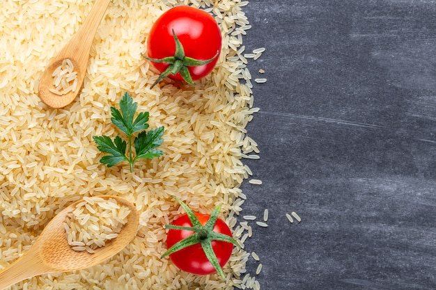 Dry golden yellow long rice with wooden spoons, ripe tomatoes cherry and fresh green parsley on dark surfce. copy space