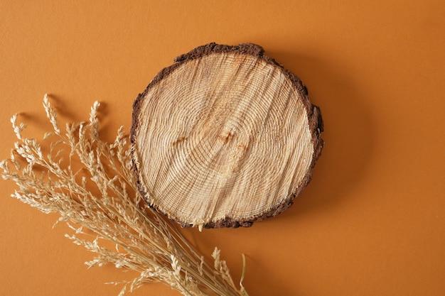 乾いた草と茶色の背景に木の表彰台の丸鋸カット、天然成分からの製品の背景コピースペース上面図モックアップ