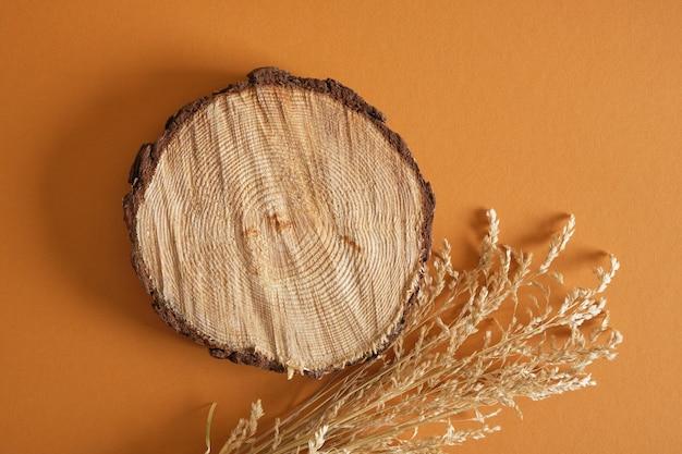 乾いた草と茶色の背景、天然成分からの製品の背景に木の表彰台の丸鋸カット