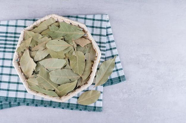 구체적인 배경에 그릇에 마른 녹색 베이 잎. 고품질 사진