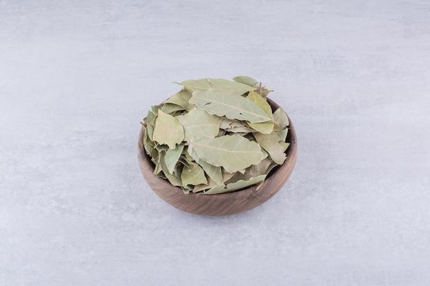 Сухие зеленые лавровые листья в деревенской чашке. фото высокого качества