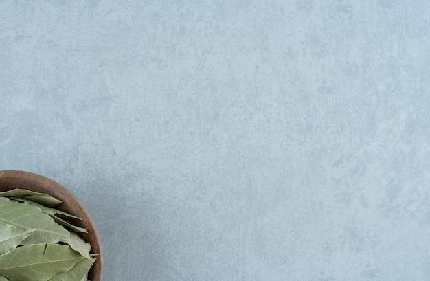 Сухие зеленые лавровые листья в деревянной чашке. фото высокого качества