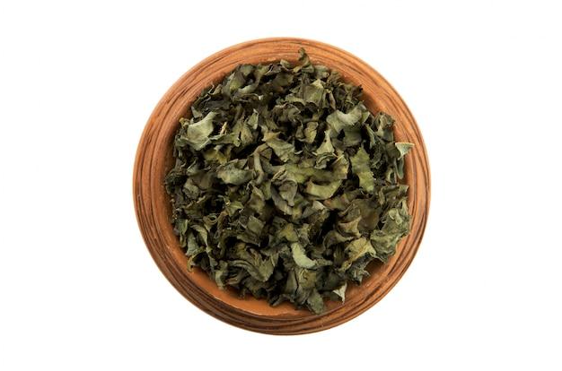 白い背景に分離された光沢のあるカップで乾燥した緑のハーブ