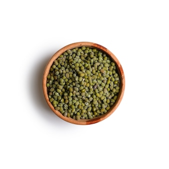 Dry green mung bean seeds in a wooden bowl, food ingredients in asian cuisine isolated on white background. top view