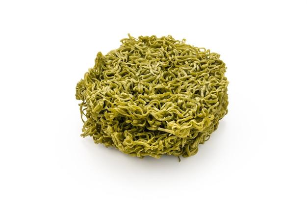 Сухая зеленая лапша или овощная лапша на изолированном белом фоне