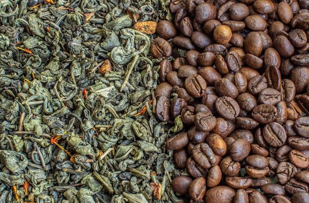 Сухие листья зеленого чая и жареные кофейные зерна. крупным планом вид сверху. понятие о кофе или зеленом чае.