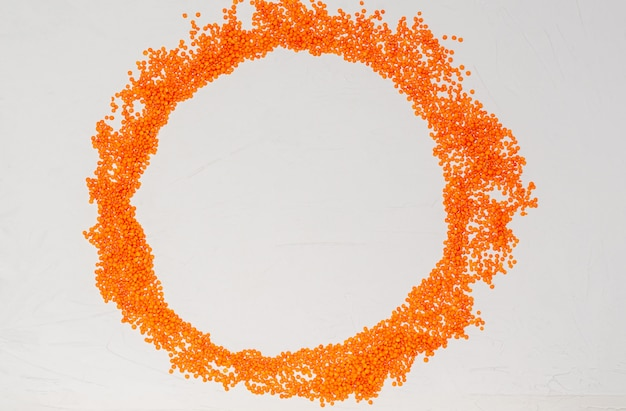 Dry groats of orange lentils for vegans in the form of a round frame for text on a white surface with copy space