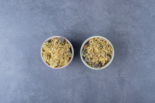 Dry healthy leaves in bowl. two small bowls full with bowl on grey background.