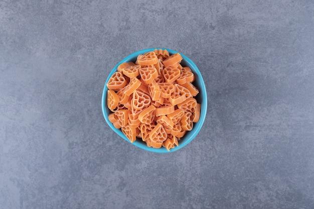 Сухие макароны в форме сердца в синей миске.