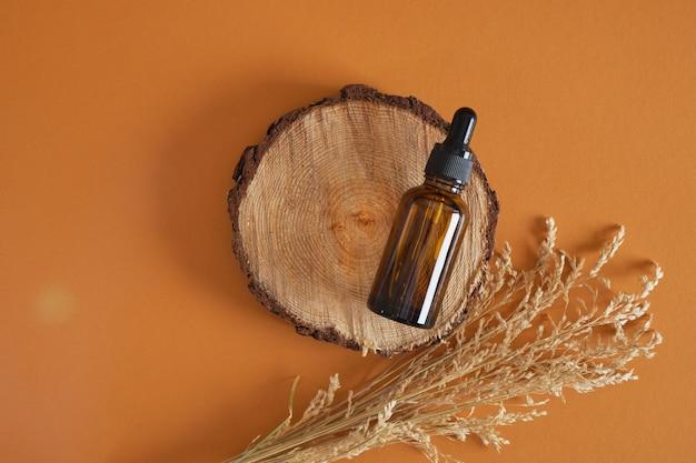 갈색 배경에 나무 연단의 둥근 컷에 피펫이 있는 마른 허브와 호박색 병, 바디 케어를 위한 오일 또는 혈청을 위한 조롱