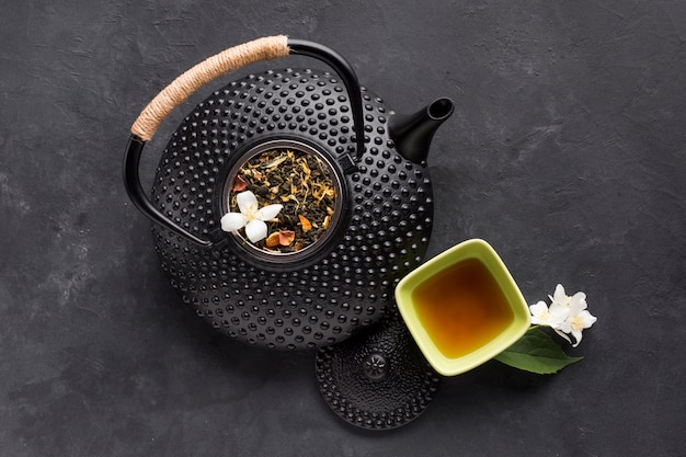 Dry herb and herbal tea with teapot on black surface