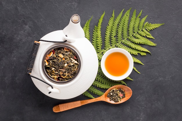 Dry herb leaves and fern leaves with herbal tea on black surface