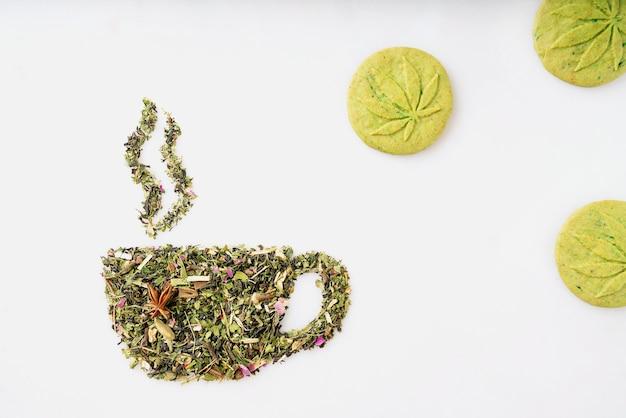 Сухие листья травяного чая в форме чашки с дымом и печеньем каннабиса