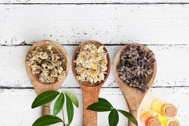 Сухие травы и эссенции на деревянный белый стол. нетрадиционная медицина. плоская планировка