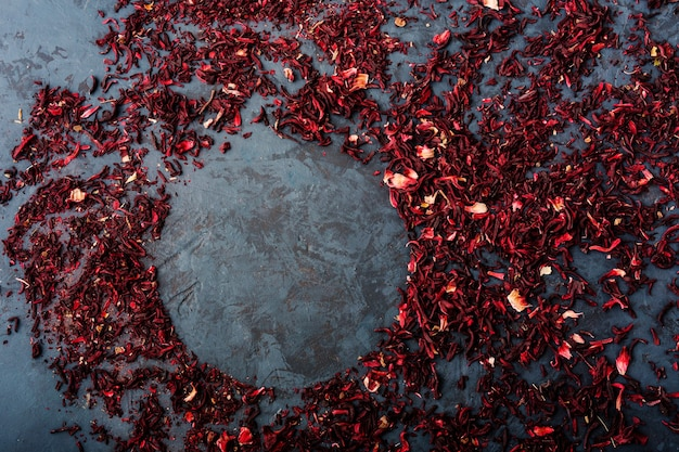 Dry hibiscus leaves scattered on a dark blue background, space for text