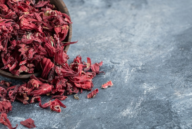 Dry hibiscus tea in wooden bowl.