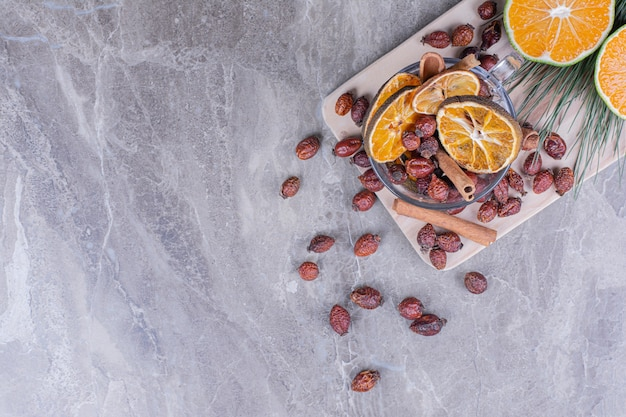 Dry hips and orange slices with fresh oranges on wooden board.