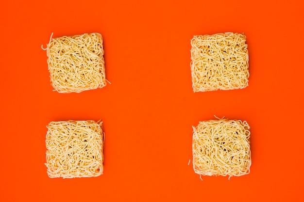 Dry instant noodles arranged on plain bright orange surface