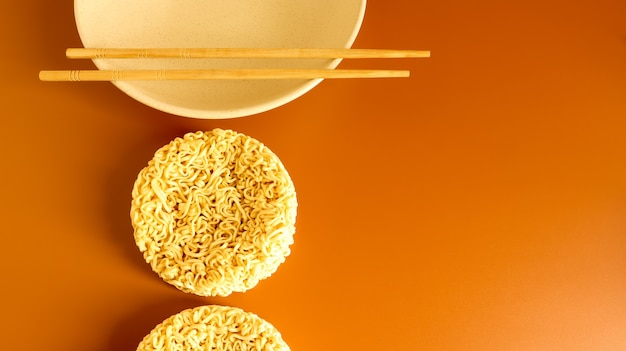 箸で皿の上に典型的な円形のインスタントラーメンを乾かします。インスタントラーメンが人間の健康に及ぼす影響。パスタ、その準備のために沸騰したお湯を注ぐのに十分です。
