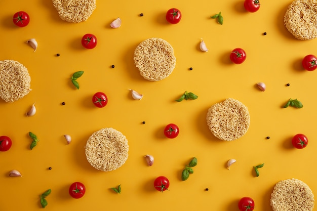 Dry instant noodles with tomatoes, garlic, basil and pepper for preparing fresh soup, yellow background. preparing qucik lunch. unhealthy eating and fast food concept. ingredients for making dish