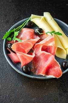 Сухой хамон итальянского прошутто серрано беллота крудо или порция пармской ветчины на столе