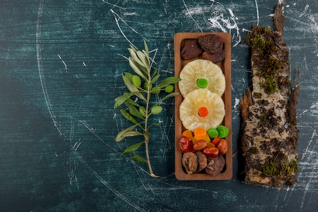 Tavola di frutta secca e gelatinosa con un pezzo di legno su un tavolo blu