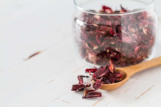 Dry karkade tea, white wood background