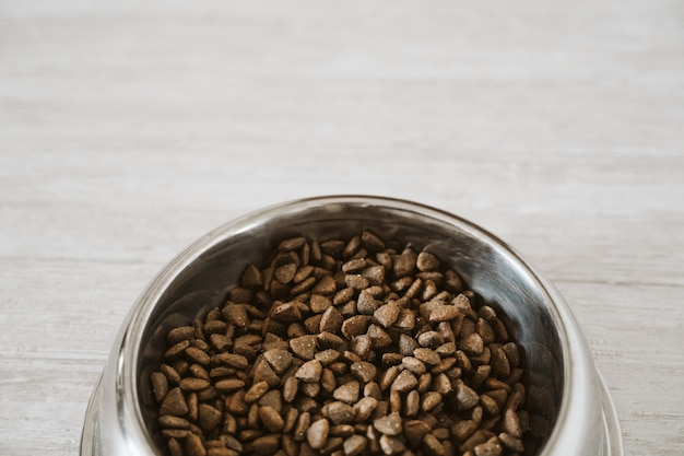 Сухой корм для собак в миске на полу