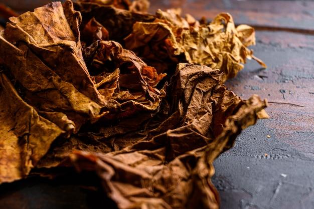 乾燥葉たばこをクローズアップnicotiana tabacumとタバコは古い木の板テーブルダークサイドビューテキスト用のスペースに葉します。