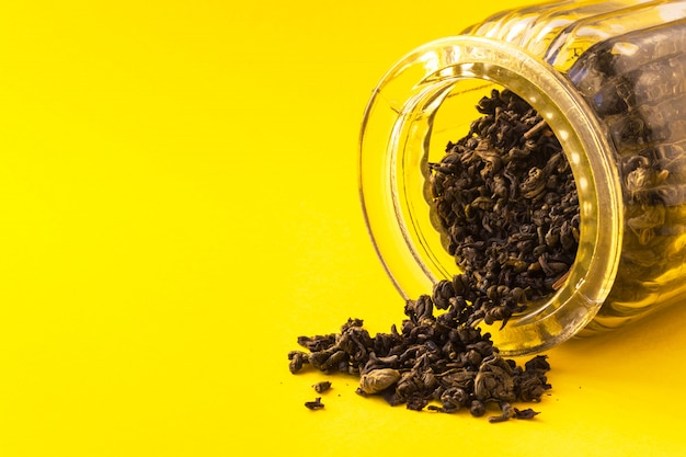 Dry leaves of black tea in glass on yellow background